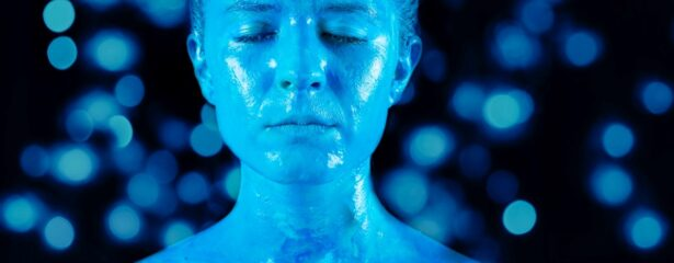 Woman's blue face with blue light spots in backgrouns